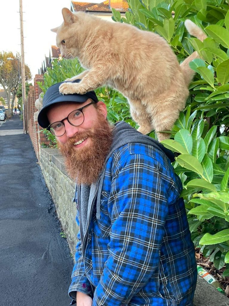 Simon stands in the street smiling at the camera with a large ginger cat perched on his shoulders and head.