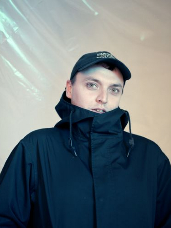 Image of Duncan wearing a black baseball cap with a black coat pulled up over his chin.