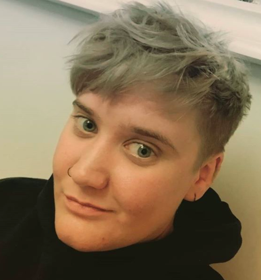 Image of Hannah with short grey/blond hair and a black hooded top