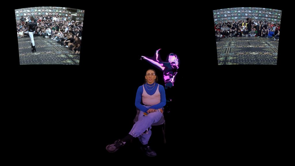 Image from VR piece Gimme One, that shows a trans woman seated with a pink heat graphic of a woman moving behind her. In the black background there are two screens to the right and left that appear to show voguing/ballroom scenes.