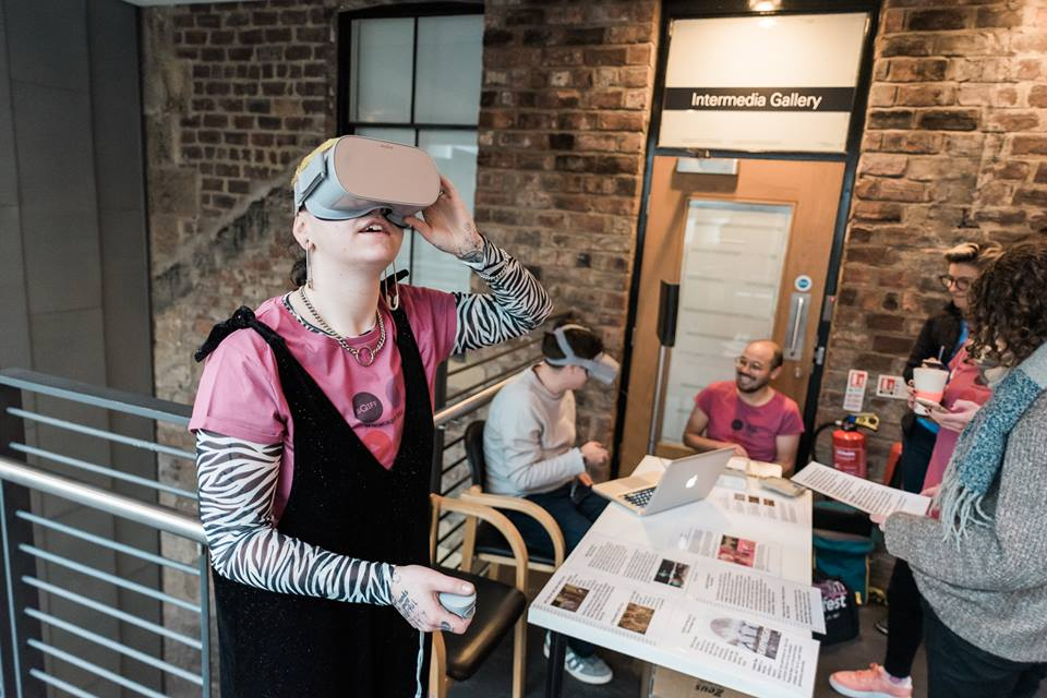 Image from SQUIFF, the Scottish Queer Film Festival. It shows a person in a pink SQUIFF t-shirt and black jumpsuit wearing a VR headset. Behind where she is standing a team of people sit around a table, some of them also in headsets.