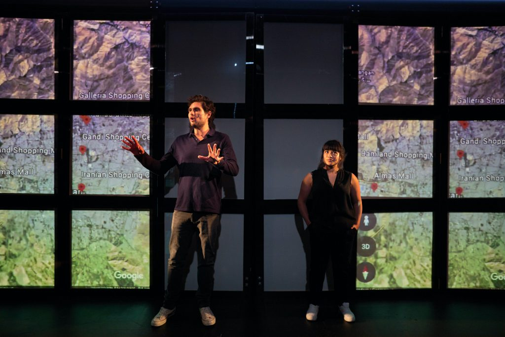 Javaad Alipoor and co-star Peyvand Sadeghian in Rich Kids. They are standing against a background of square screens that show a topological google map of Tehran.