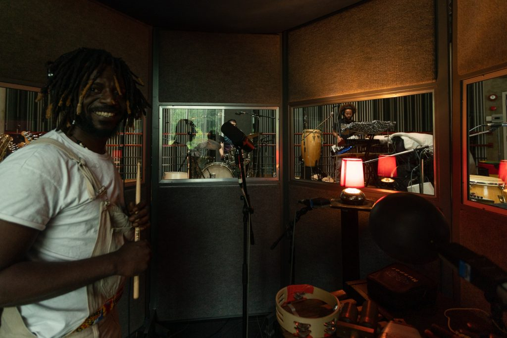 Imgae of a man from Onipa in the studio, smiling into the camera and holidng a drumstick. In the background you can see windows into the rest of the studio where other band members are.