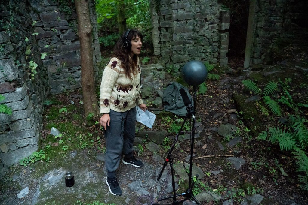 Image of a female singer from 9Bach standing in among castle ruins, wearing headphones and singing into a microphone
