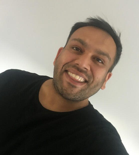 Tony smiles at camera wearing a black t-shirt