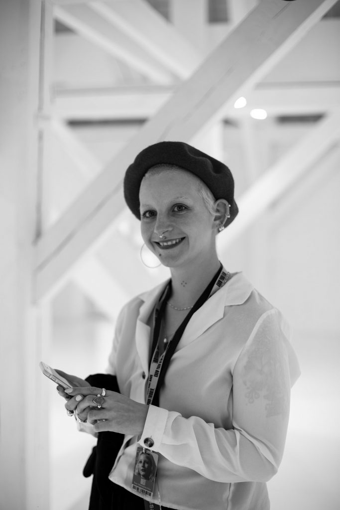 A young white woman photographed in black and white wearing a beret and smiling at camera