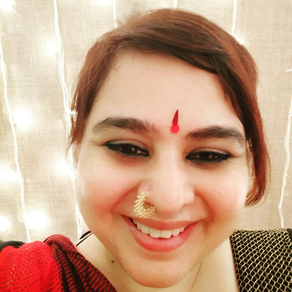 Headshot of young indian woman smiling into camera with nose ring and red hair