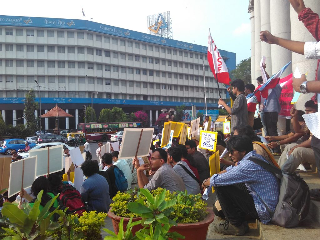 Protest in India with young people sitting on steps holding placards