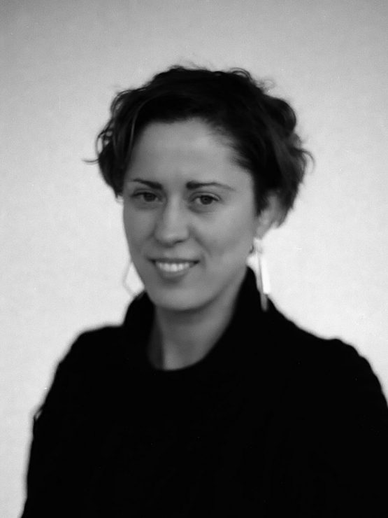 A Black & White Image of Teresa smiling into the camera. Teresa has short hair and is wearing a black jumper with large square earrings.