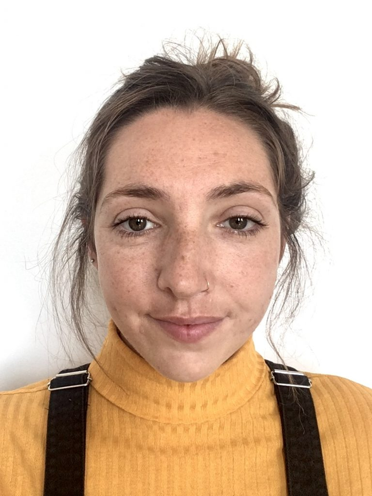 A headshot of Jess, a white woman with brown hair tied up and a nose piercing. Jess is wearing a yellow roll-neck top and black dungarees.