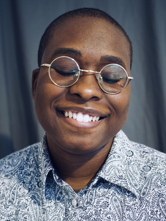 A image of Ashanti smiling into the camera with her eyes closed. Ashanti is a black woman with short black hair and round silver glasses. She is wearing a white and blue paisley shirt.