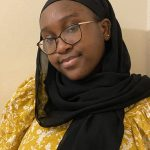 A headshot of Bashirat who is smiling into the camera in front of a pale background. Bashirat is wearing a yellow floral top, black headscarf and has black and gold glasses.