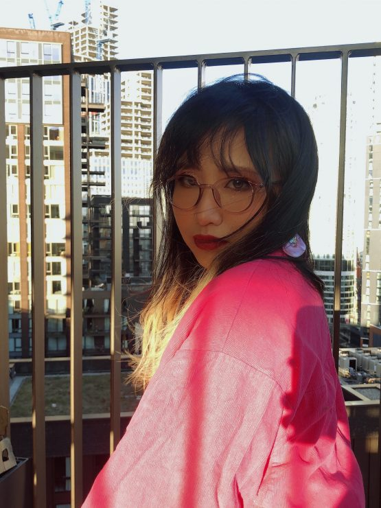 A image of Vivienne who is staring into the camera with sky scrapers behind her. She has long brown hair and pair of round glasses with pink frames. She is wearing a pink jumper.