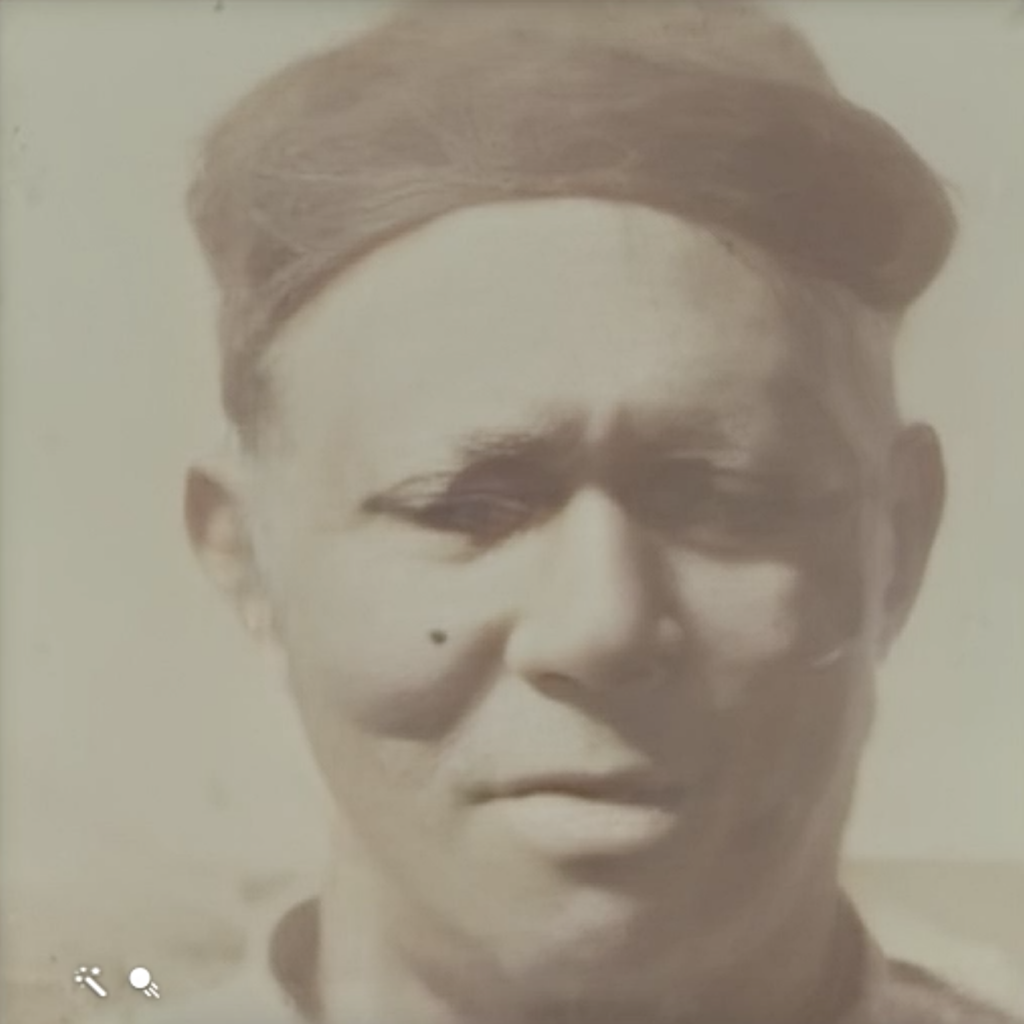 A sepia portrait of a man wearing a dark hat and a collarless shirt, looking down