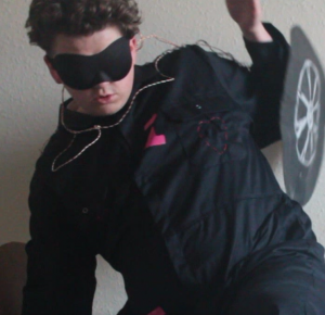 Image of Oma Keeling wearing a mask and a black boiler suit. They have short dark hair and are moving energetically