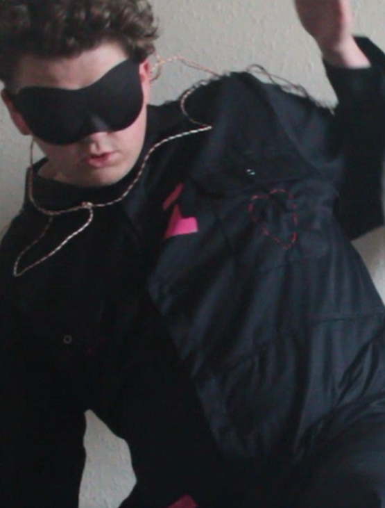 A headshot of Oma who is looking away from the camera in front of a pale background. Oma is wearing a black boiler suit with pink embroidery. Oma has an eye mask on and ear plugs and is moving quickly in the image.