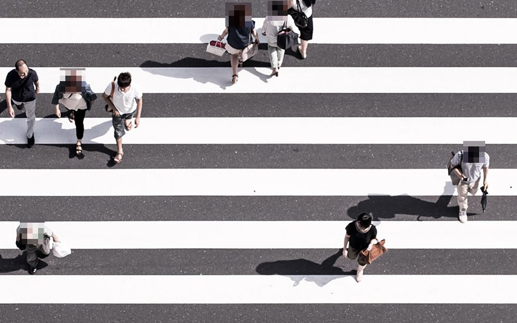 An image of a zebra crossing with several people walking across. Five of the people have been pixelated.
