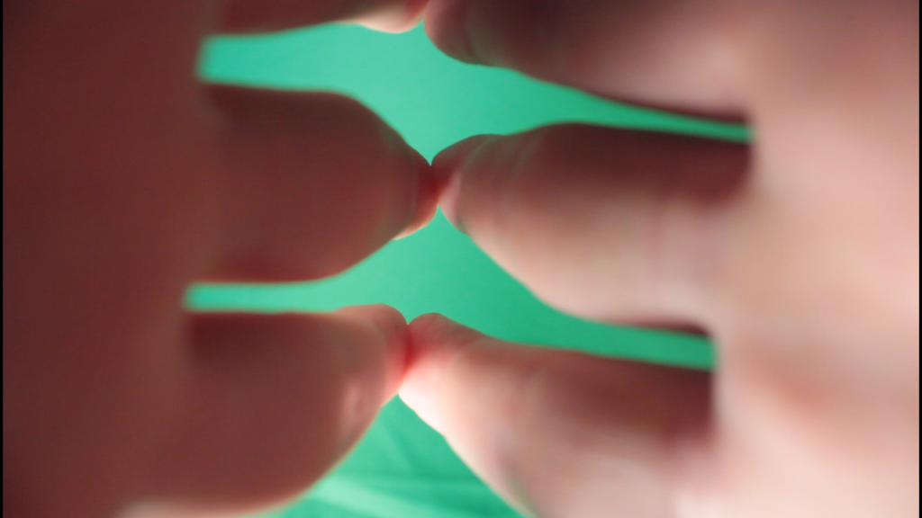 Two hands touch at the fingers, against a green background