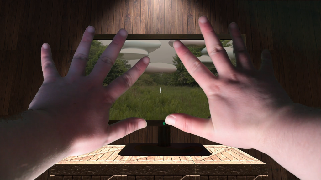 A pair of hands stretch out towards a computer-generated image of a wooden desk with a computer on it. On the screen is a picture of a park with green grass and a grey sky